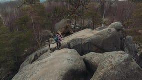 攀登下来峰顶的旅游夫妇的鸟瞰图 健康生活方式,挑运 极端冒险 令人愉快 影视素材