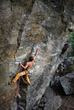 攀登与套住的年轻人一个岩石 绳索上升 免版税库存图片