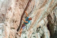 攀登严厉伸出的高橙色岩石的男性运动员 免版税库存照片