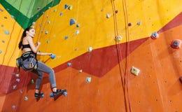攀登在健身房的活跃妇女墙壁 免版税库存照片