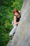 攀登在夏时的运动妇女峭壁墙壁 免版税库存照片