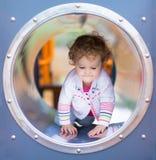 攀登在操场的逗人喜爱的卷曲女婴一张幻灯片 免版税库存照片