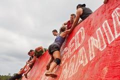 攀登在极端障碍桩种族的墙壁的竞争者奋斗 免版税库存照片