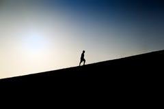 攀登小山的一个人的剪影 库存图片