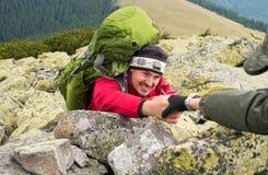 攀登山的手帮助的远足者 免版税库存图片
