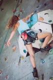 攀登岩石墙壁的一个少年室内 免版税库存图片