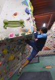 攀登岩石墙壁的一个日本人室内 免版税库存图片