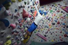 攀登岩石墙壁的一个日本人室内 免版税图库摄影