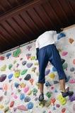 攀登岩石墙壁的一个日本人室内 免版税库存照片