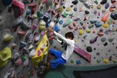 攀登岩石墙壁的一个日本人室内 库存照片
