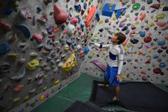 攀登岩石墙壁的一个日本人室内 库存图片