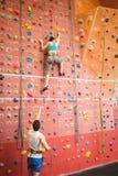 攀登岩石墙壁的妇女 图库摄影