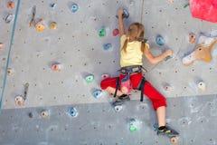 攀登岩石墙壁的小女孩 库存照片