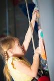 攀登岩石墙壁的小女孩 免版税库存照片