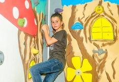 攀登岩石墙壁的小男孩室内 库存照片