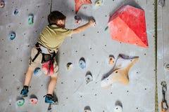 攀登岩石墙壁的小男孩室内 免版税库存图片