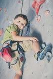 攀登岩石墙壁的小男孩 免版税图库摄影