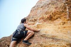 攀登岩石峭壁的年轻运动员 库存图片