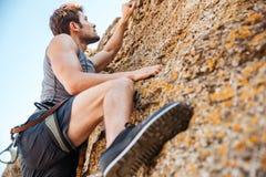 攀登岩石峭壁的年轻运动员 图库摄影