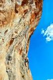 攀登峭壁的攀岩运动员 免版税图库摄影