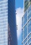 攀登摩天大楼的外部墙壁的维护工作者 库存图片