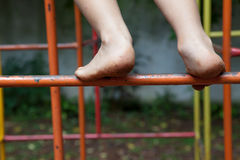 攀登操场的小孩肮脏的脚 图库摄影