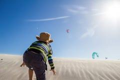 攀登有风沙丘的激动的小男孩观看风筝冲浪者 免版税图库摄影