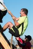 攀登有绳索的人奋斗墙壁在极端障碍桩 库存图片