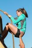攀登有绳索的妇女奋斗墙壁在极端障碍桩 免版税图库摄影