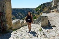 攀登楼梯台阶的少妇在老镇马泰拉、联合国科教文组织世界遗产名录站点和文化的欧洲首都2019年 库存图片