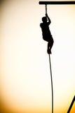 攀登绳索的人的剪影 免版税图库摄影