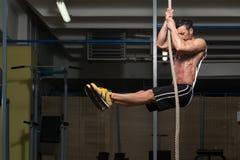 攀登绳索的健身运动员 图库摄影