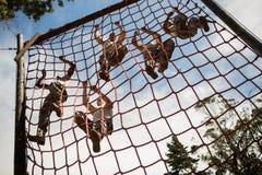 攀登绳索的军事战士在障碍桩期间 图库摄影