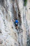 攀登陡峭的石灰石峭壁的一个人 库存图片