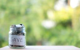攒钱到现金未来投资的瓶里,有绿色背景 免版税图库摄影