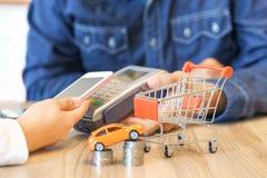 支付一辆新的汽车的妇女通过有红色购物车的智能手机 免版税库存图片