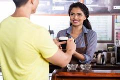 支付与信用卡的咖啡的男性顾客 库存照片