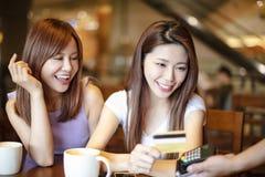 支付与信用卡的妇女在咖啡馆商店 免版税库存照片