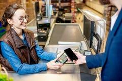 支付与在收款机的卡片有愉快的出纳员的 免版税库存照片
