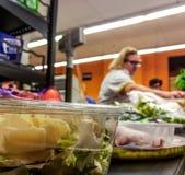支付产品的顾客在结算离开 在传送带的食物在超级市场 免版税图库摄影