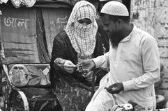 支付人力车车费的小姐对一名人力车制帽工人在孟加拉国 库存照片