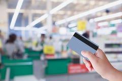 支付使用在超级市场结算离开出纳员的信用卡 免版税图库摄影