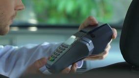 支付出租汽车乘驾的妇女通过在智能手机的应用,不接触的付款 股票视频