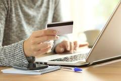 支付在与信用卡的线的妇女手 免版税库存图片