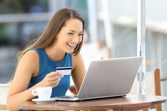 支付在与信用卡的线的愉快的妇女 库存图片
