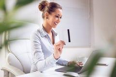 支付在互联网上的女商人 免版税库存图片
