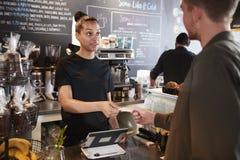 支付在咖啡店的顾客使用信用卡 免版税库存照片
