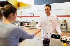 支付在快餐餐馆的卖主和顾客 免版税图库摄影