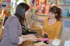 支付玩具的年轻母亲在玩具店出纳员 库存图片
