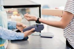 支付由巧妙的手表的无法认出的妇女 免版税库存图片